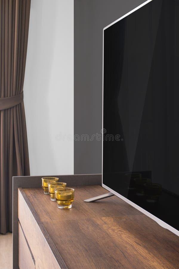 Geleide TV op TV-tribune met kaarsen en gordijn, grijze muur stock afbeelding