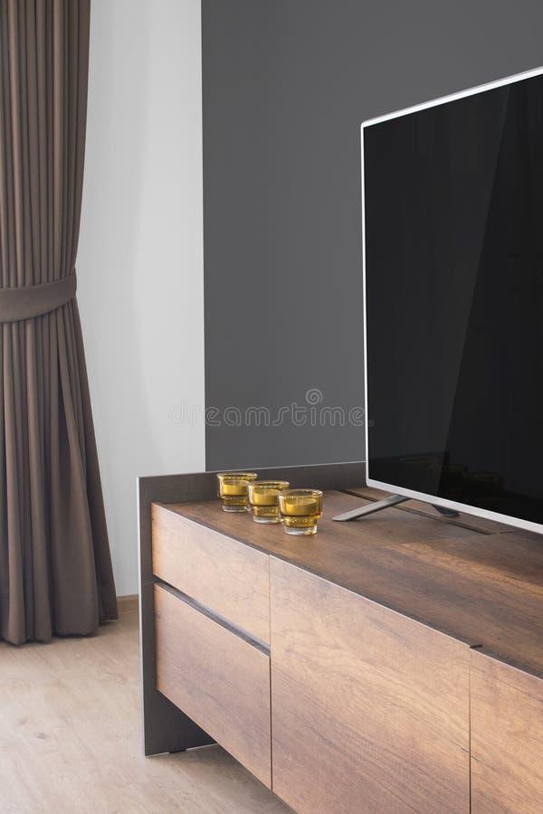 Geleide TV op TV-tribune met kaarsen en gordijn, grijze muur royalty-vrije stock foto