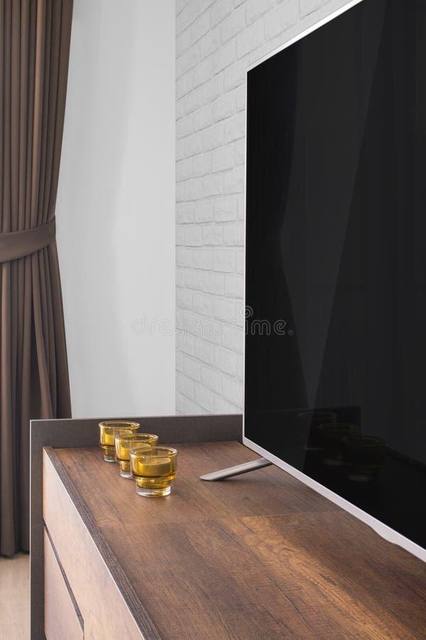 Geleide TV op TV-tribune met kaarsen en gordijn, witte bakstenen muur royalty-vrije stock foto's