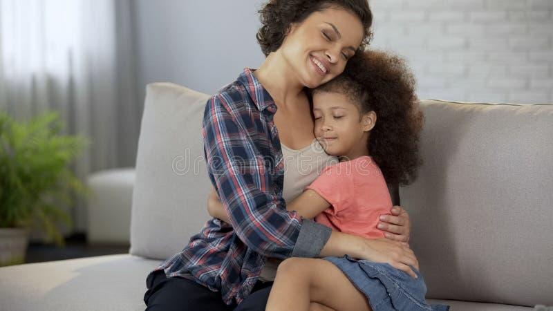 Geliebte Mutter, die fest ihre kleine Tochter, volles Vertrauen und Neigung umarmt stockbilder