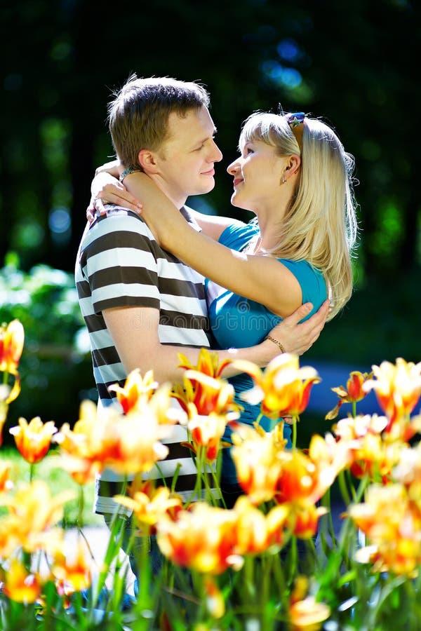 Geliebtmann und -mädchen unter roten gelben Blumen lizenzfreies stockfoto