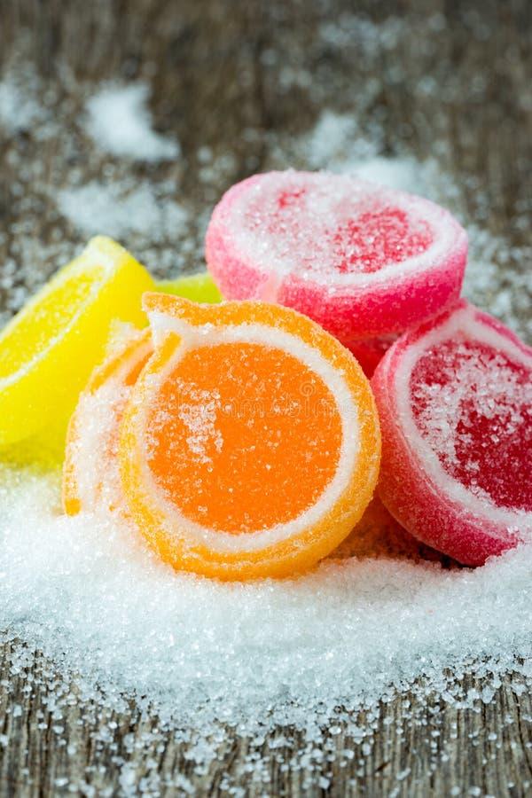Gelieren Sie Bonbon, Aromafrucht, der Süßigkeitsnachtisch, der auf hölzernem backgr bunt ist stockbilder