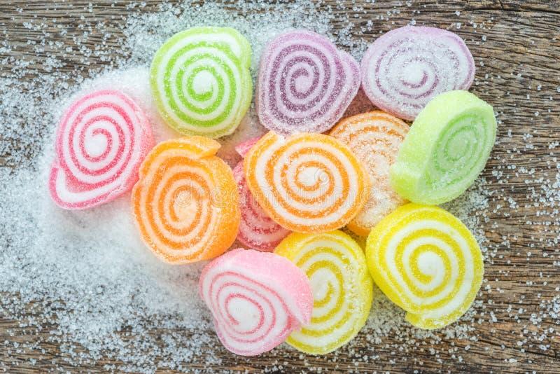 Gelieren Sie Bonbon, Aromafrucht, der Süßigkeitsnachtisch, der auf hölzernem backgr bunt ist stockfotos