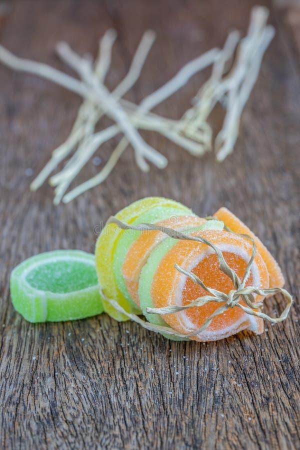 Gelieren Sie Bonbon, Aromafrucht, der Süßigkeitsnachtisch, der auf hölzernem bunt ist stockfoto