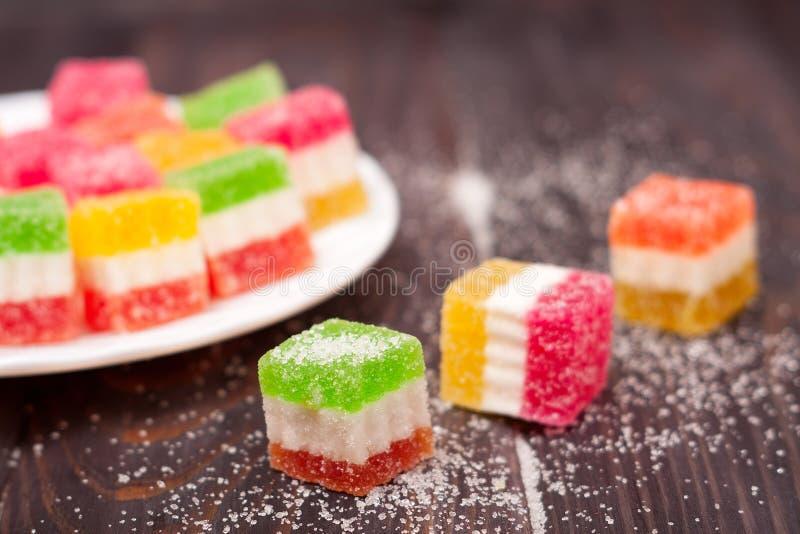 Gelieren Sie Bonbon, Aromafrucht, der Süßigkeitsnachtisch, der auf hölzernem Hintergrund bunt ist stockfotografie