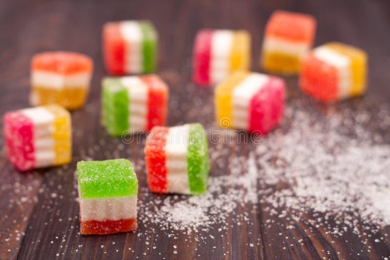 Gelieren Sie Bonbon, Aromafrucht, der Süßigkeitsnachtisch, der auf hölzernem Hintergrund bunt ist stockfoto