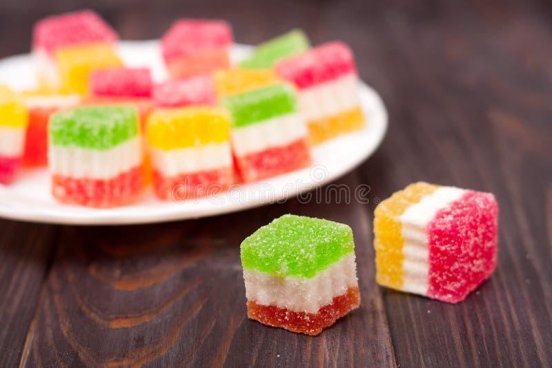 Gelieren Sie Bonbon, Aromafrucht, der Süßigkeitsnachtisch, der auf hölzernem Hintergrund bunt ist lizenzfreie stockbilder