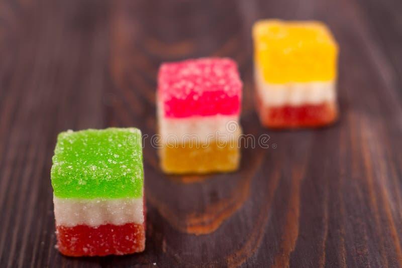 Gelieren Sie Bonbon, Aromafrucht, der Süßigkeitsnachtisch, der auf hölzernem Hintergrund bunt ist lizenzfreies stockfoto