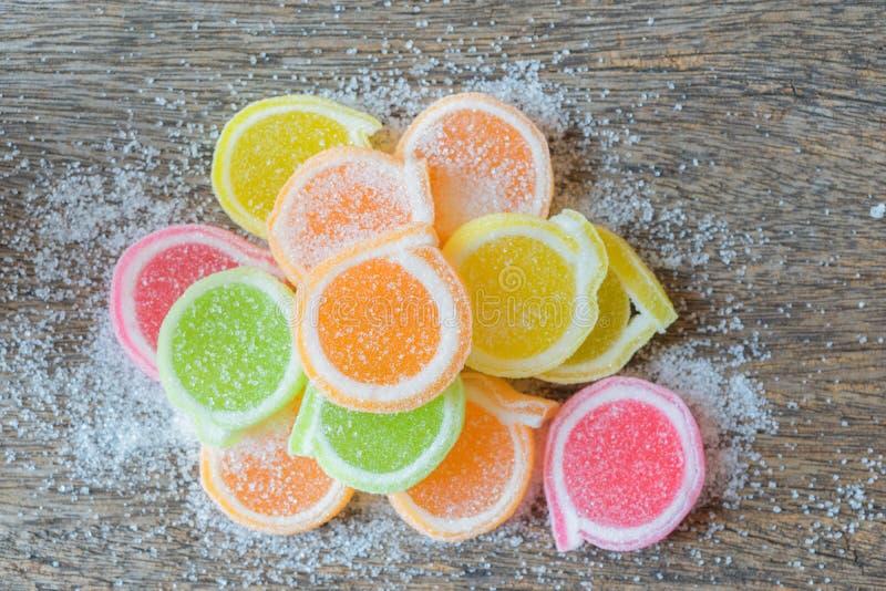 Gelieren Sie Bonbon, Aromafrucht, der Süßigkeitsnachtisch, der auf Holz bunt ist lizenzfreie stockbilder