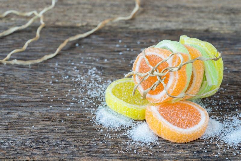 Gelieren Sie Bonbon, Aromafrucht, der Süßigkeitsnachtisch, der auf Holz bunt ist lizenzfreie stockfotografie
