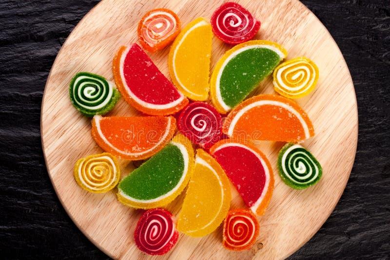 Gelieren Sie Süßigkeitzitrusfrucht in den Formularläppchen, die auf einem weißen Hintergrund getrennt werden Gelieren Sie Süßigke stockfoto