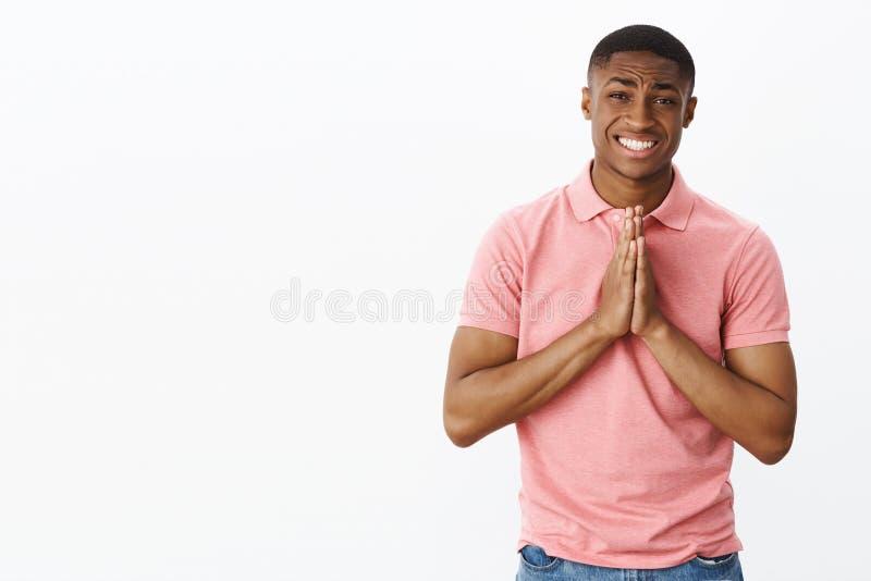 Gelieve te vereisen werkelijk uw hulp De charmante oprechte Afrikaanse Amerikaanse jonge kerel die om gunstholding vragen dient b stock fotografie