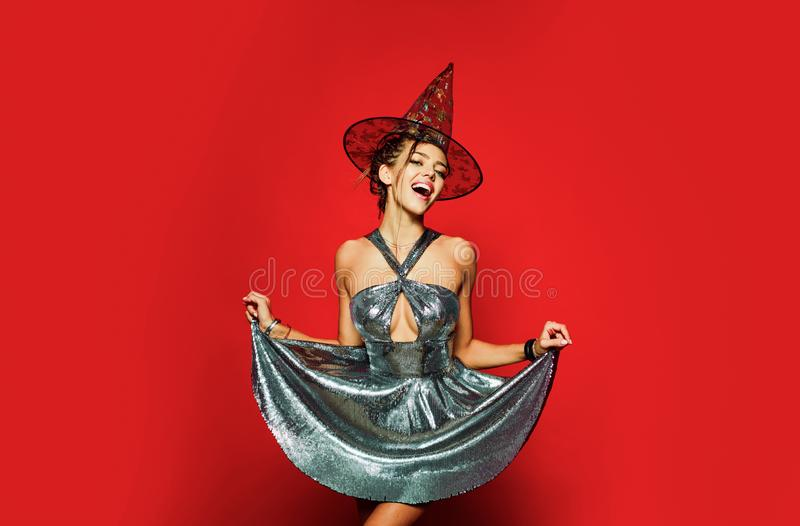 Gelightful blonde lady dressed in a fashionable dress on red background. Halloween dresses and witch costumes design royalty free stock photo