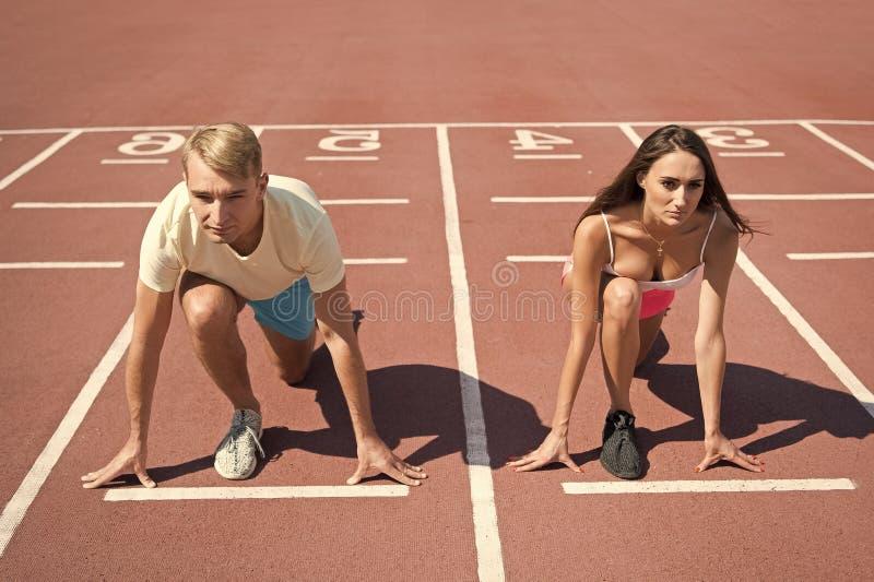 Gelijk krachtenconcept Man en vrouwen laag de lopende oppervlaktestadion van de beginpositie Lopend de concurrentie of geslachtsr royalty-vrije stock fotografie