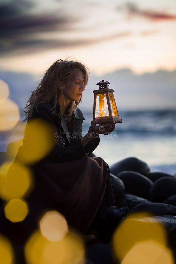 Gelijk makend na zonsondergang bij het strand, zit de blondevrouw met lantaarn naast het overzees, licht bokeh stock fotografie
