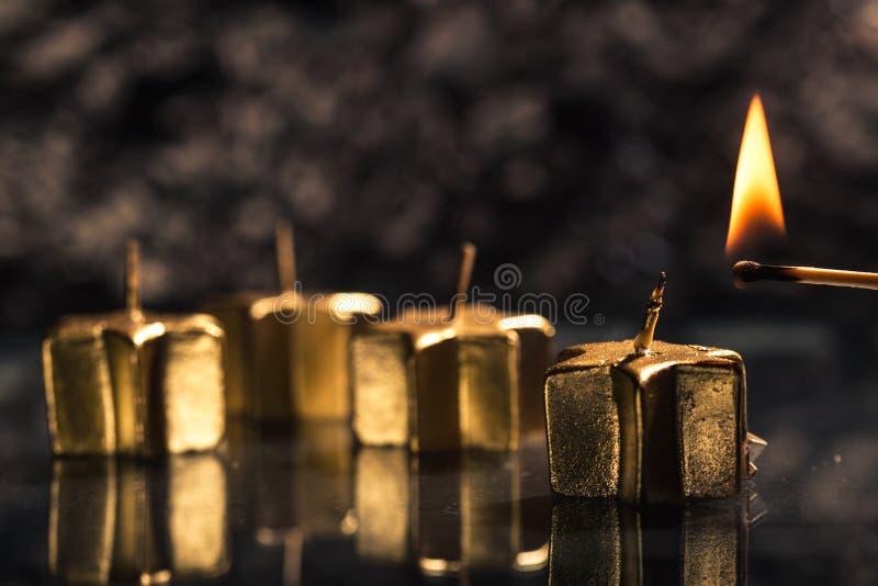 Gelijke die de eerste gouden komstkaars aansteken stock afbeeldingen