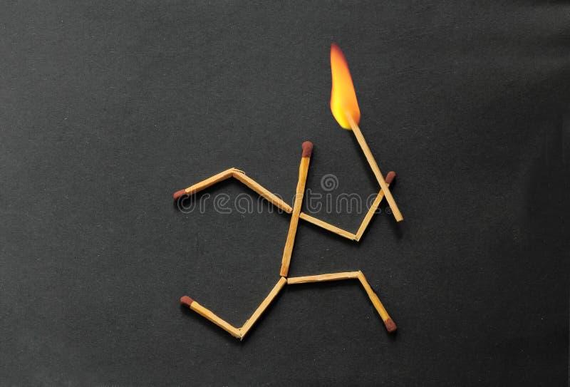 Gelijkestok die met brand op hoofd lopen stock fotografie