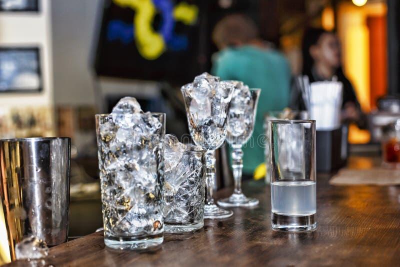 Gelo em vidros de cocktail na barra Preparação do cocktail imagens de stock royalty free
