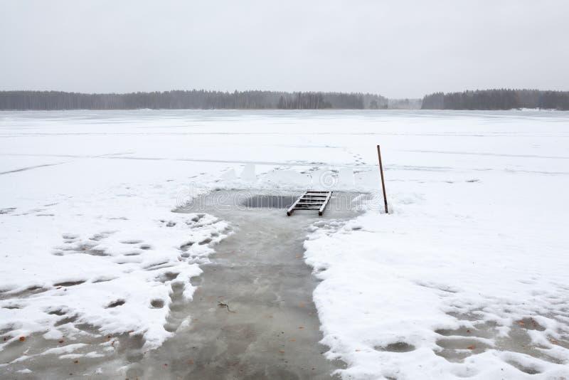 Gelo-furo no lago para a natação do inverno Escada e pá de madeira para a acessibilidade foto de stock
