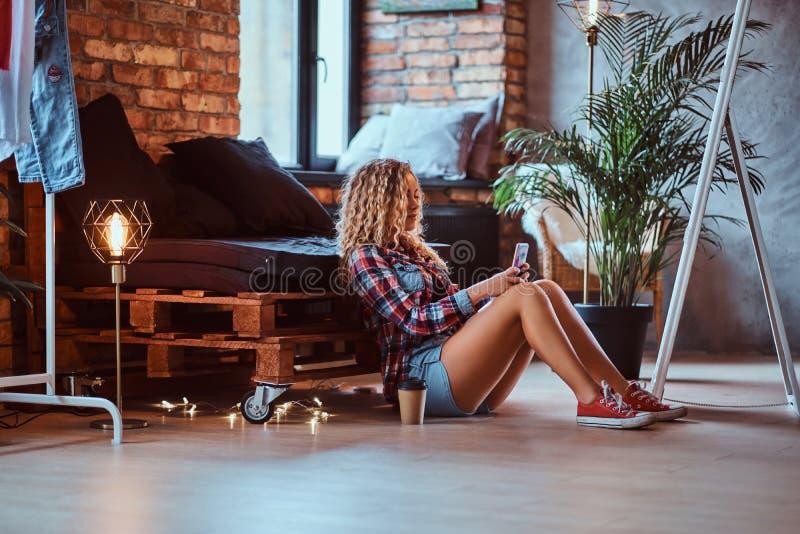 Gelockte blonde Frau sitzt nahe bei dem Palettensofa beim Schauen zu ihrem Smartphone lizenzfreie stockfotos