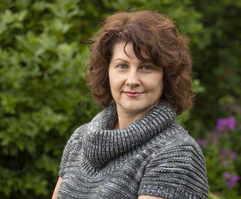 Gelockte Frau in der grauen Strickjacke auf der Natur lizenzfreies stockfoto