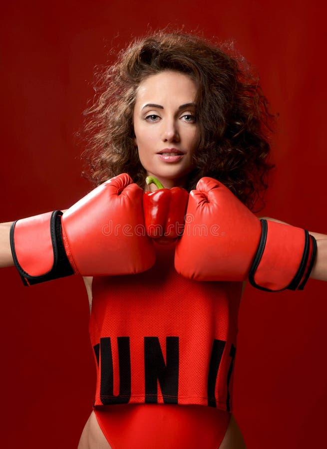 Gelockte Frau des schönen Sports mit den roten Boxhandschuhen lizenzfreie stockbilder