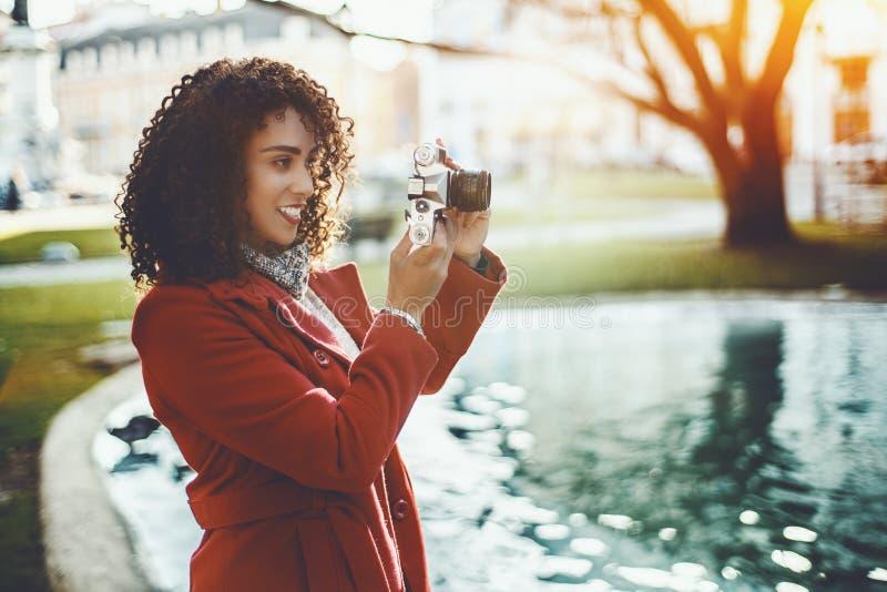 Gelockte Frau nahe Teich mit Weinlesekamera stockfotos