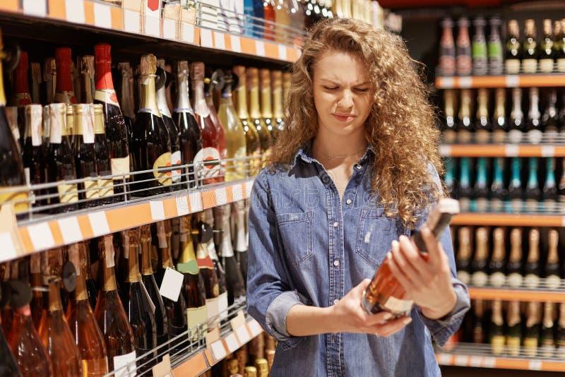 Gelockte junge Frau der Unzufriedenheit in der Denimkleidung betrachtet mit unglücklichem Ausdruck Flasche Wein, liest Informatio stockbilder