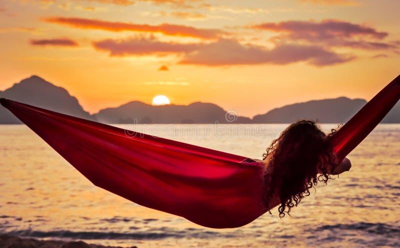 Gelockte junge Frau, die in einer roten Hängematte auf einer Tropeninsel genießt den Sonnenuntergang sich entspannt stockbild