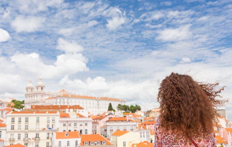 Gelockte junge Frau mit Wind in ihrem Haar betrachtet das schöne Li lizenzfreies stockbild