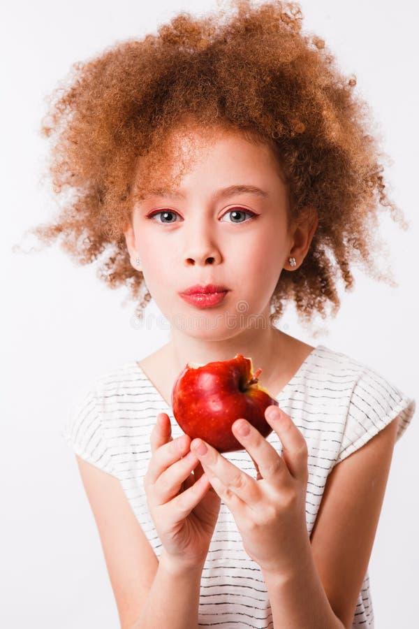 Gelockte Mutter und Tochter essen große rote Äpfel auf einem hellen Hintergrund stockfotos