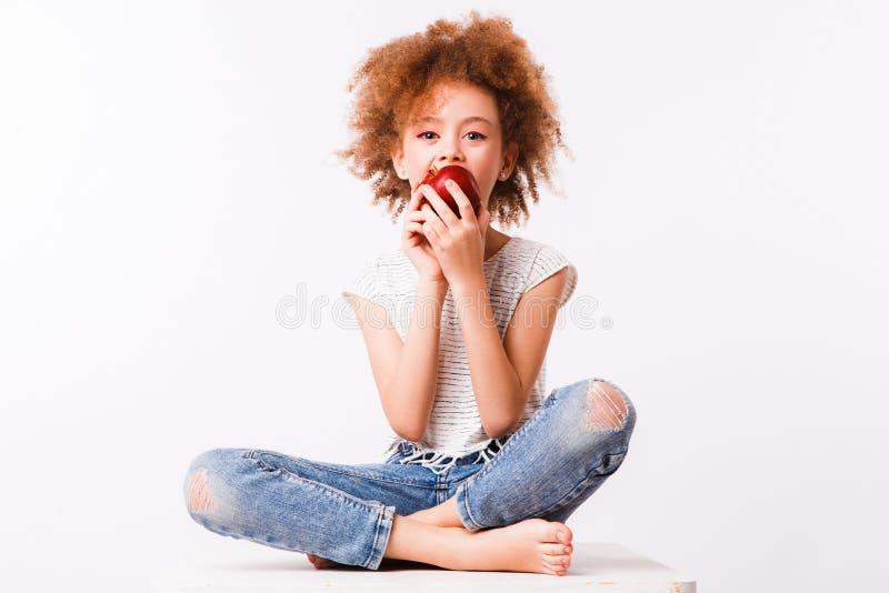 Gelockte Mutter und Tochter essen große rote Äpfel auf einem hellen Hintergrund lizenzfreie stockfotos