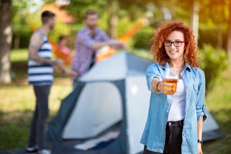 Gelockte Rothaarigefrau bietet ein Glas Bier an stockbilder