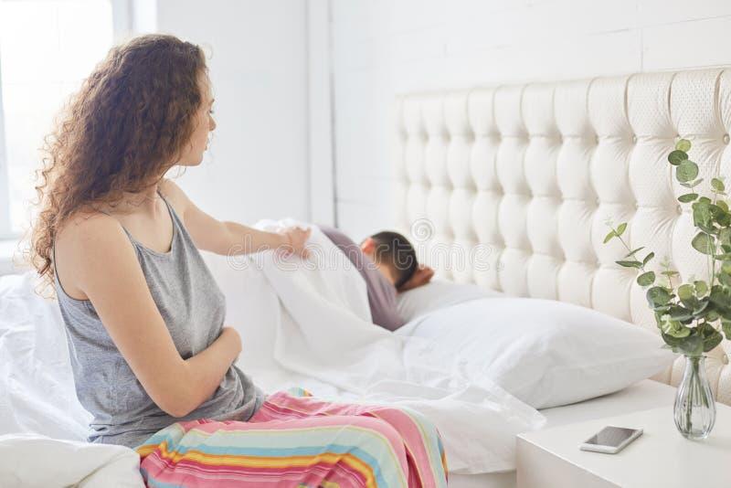 Gelockte Schönheit in den Pyjamas sitzt auf der Seite des Betts, gekleidet in den zufälligen Pyjamas, Versuche, um ihren Ehemann  stockfotografie