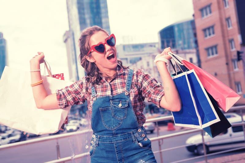 Gelockte strahlende Frau, die nach dem Einkauf extrem emotional und nett sich fühlt stockbilder