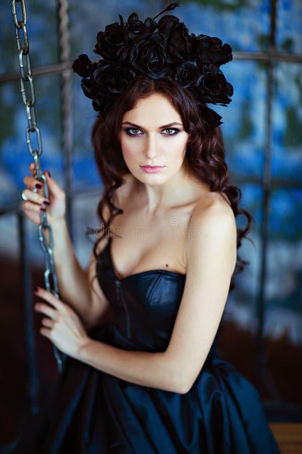 Gelockter Brunette mit einem Kranz von schwarzen Blumen sitzt unter Stromkreisen stockfoto