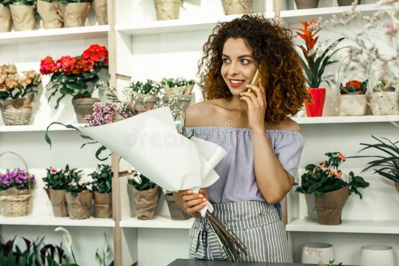 Gelockter Florist, der ihren Freund beim Haben des Bruches von der Arbeit anruft lizenzfreie stockfotos