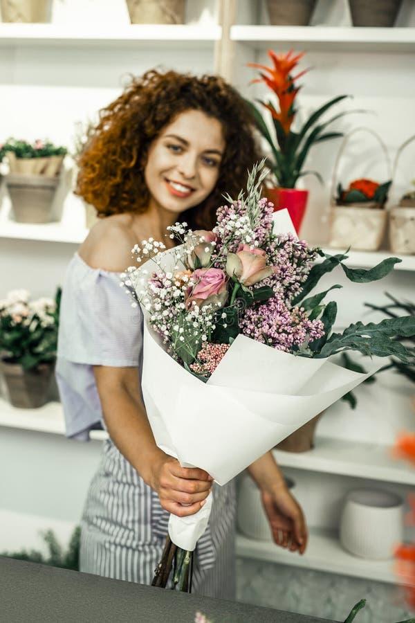 Gelockter Florist mit den hellen Lippen, die schöne Blumen im Blumengeschäft betrachten stockfoto