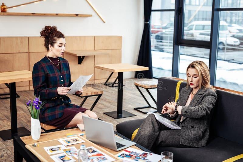 Gelockter hilfreicher Sekretär, der mit ihrem erfolgreichen wohlhabenden Chef spricht stockbilder
