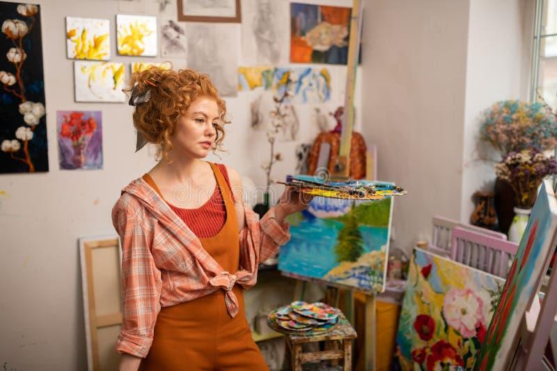 Gelockter junger Künstler, der beim Arbeiten an neuem Bild durchdacht sich fühlt lizenzfreies stockbild