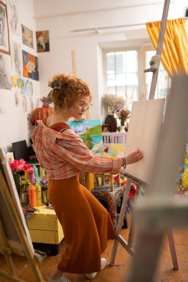Gelockter junger Künstler, der am Wochenende das Fühlen entspannt zeichnet lizenzfreies stockfoto