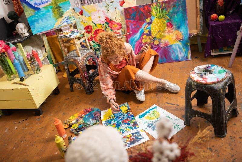Gelockter Künstler, der auf Boden sitzt und ihre Bilder beendet lizenzfreies stockfoto