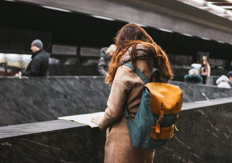 Gelockter roter Hauptmädchenreisender der jungen Frau mit Rucksack und Karte in der U-Bahn stockbild