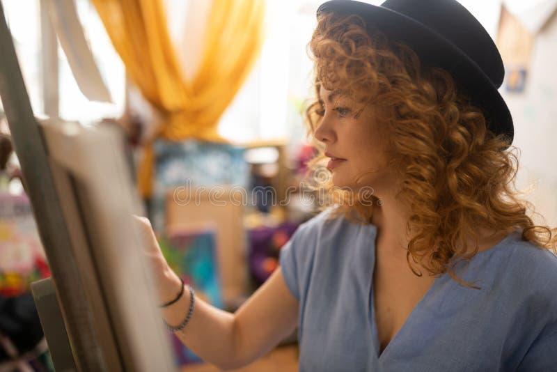 Gelockter rothaariger Künstler, der Stellung des schwarzen Hutes nahe Segeltuch trägt stockfotos