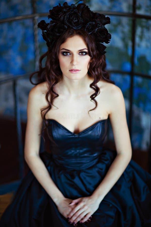 Gelockter schöner Brunette mit einem Kranz des schwarzen Blumensitzens stockbilder