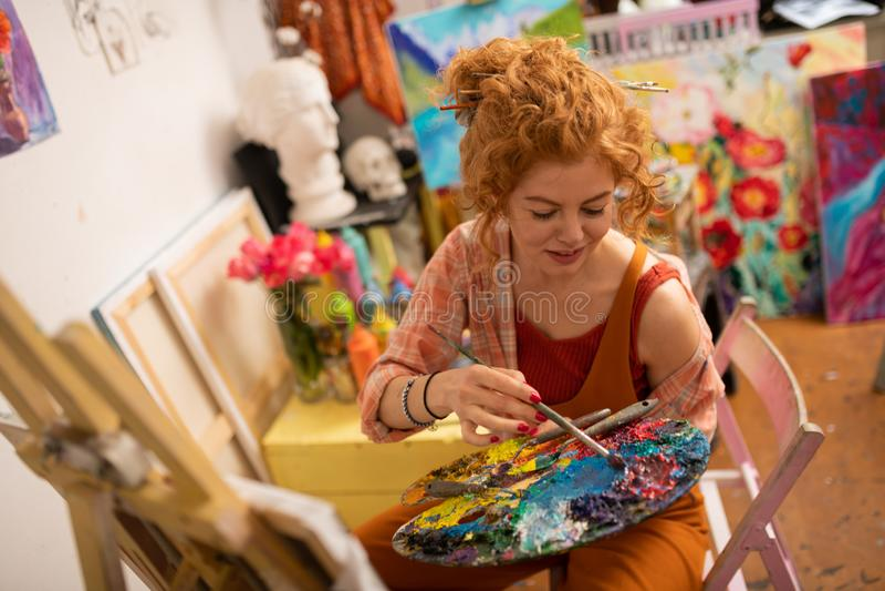 Gelockter viel versprechender Künstler, der mit der Gouache sitzt nahe Segeltuch färbt stockfotografie