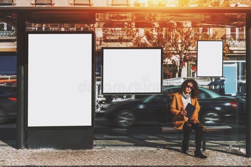 Gelocktes Frau iside der StadtBushaltestelle lizenzfreie stockbilder
