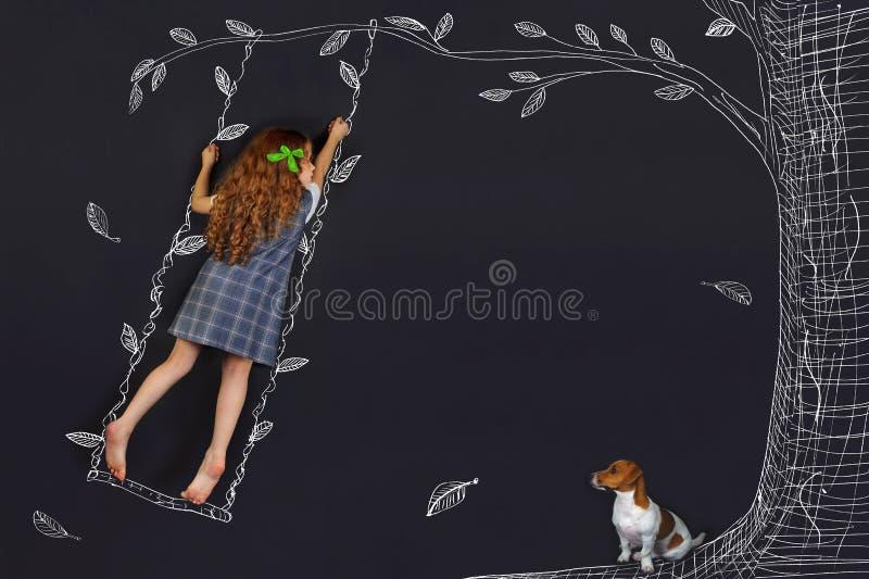 Gelocktes Mädchen des Frühlinges auf einem Schwingen stockbild