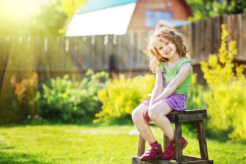 Gelocktes Mädchen sitzt auf einem Stuhl im Yard eines Landhauses stockbild