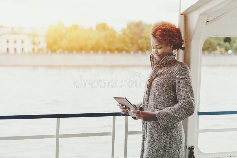 Gelocktes nachdenkliches Mädchen mit digitaler Tablette auf Schiffsplattform lizenzfreies stockbild
